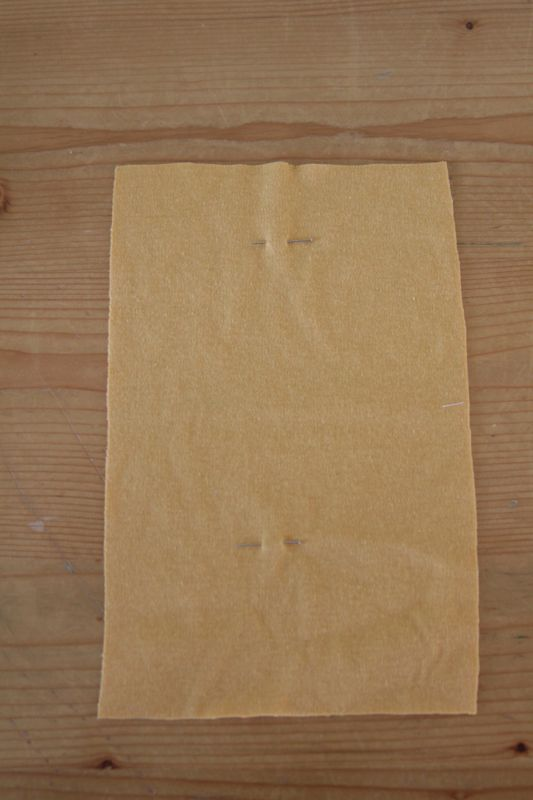 Piece of yellow fabric with pin new the top and pin new the bottom