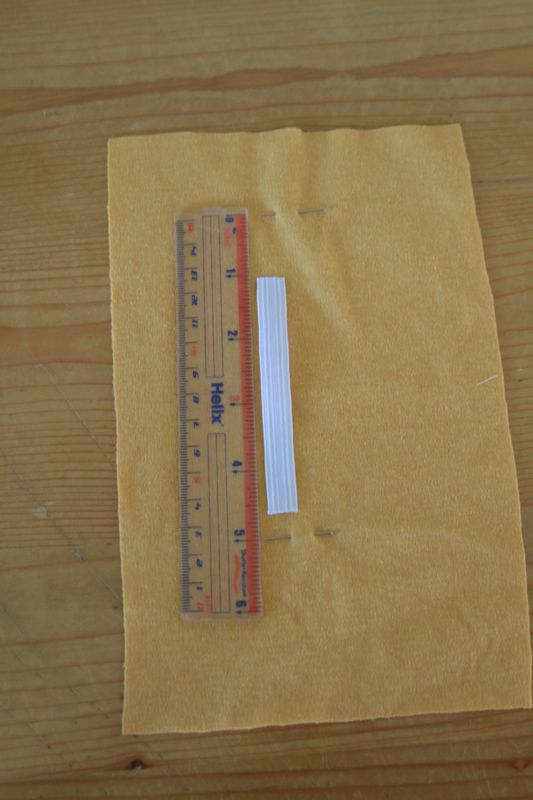 Yellow fabric pinned, with ruler and piece of elastic