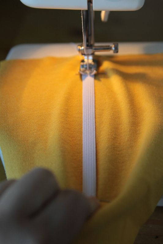 Yellow fabric and elastic on sewing machine with elastic stretched so fabric is flat