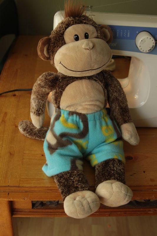 A stuffed animal monkey wearing pajama shorts