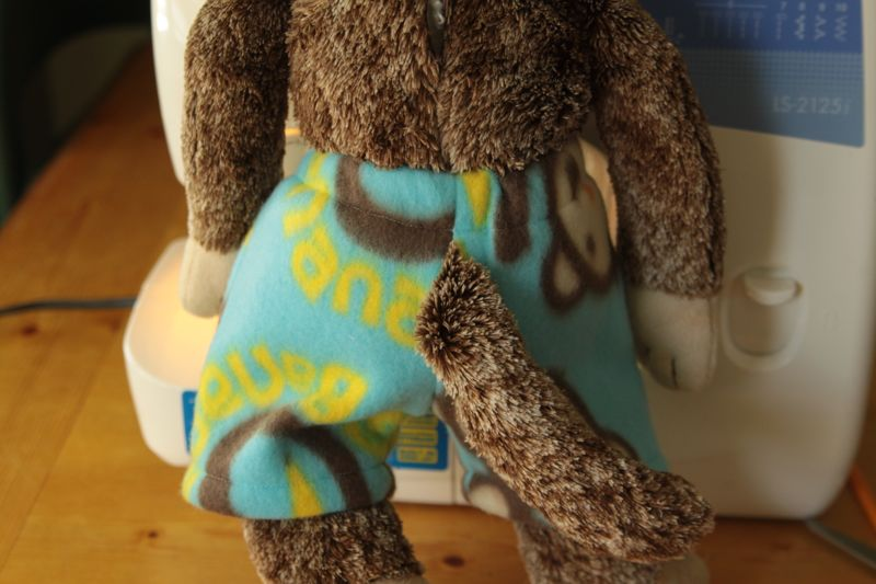 A stuffed animal monkey with tail coming out of back of shorts