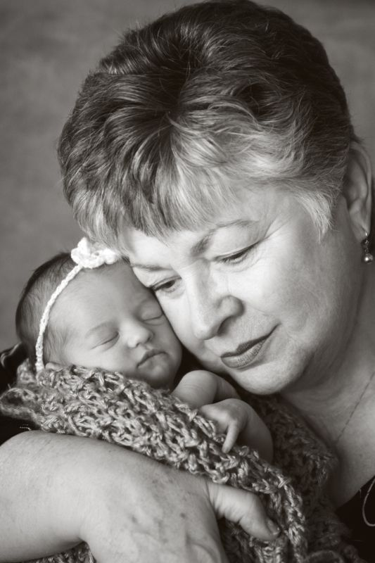 A Grandma leaning her head toward a newborn baby