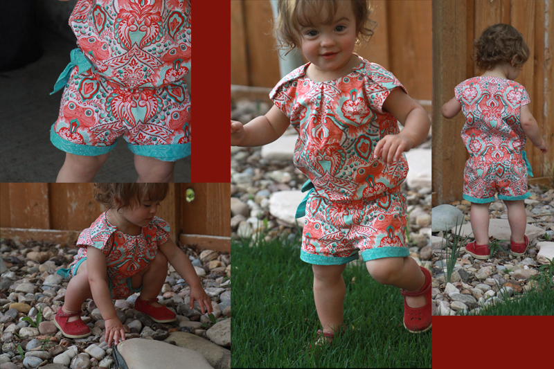 A little girl wearing a brightly colored romper