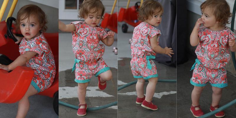 A little girl wearing a shortie romper