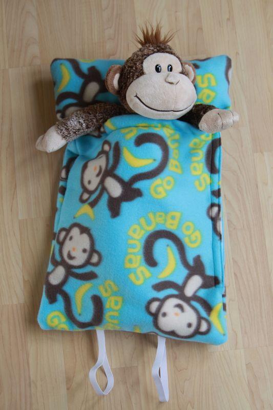 A stuffed animal monkey inside homemade fleece sleeping bag