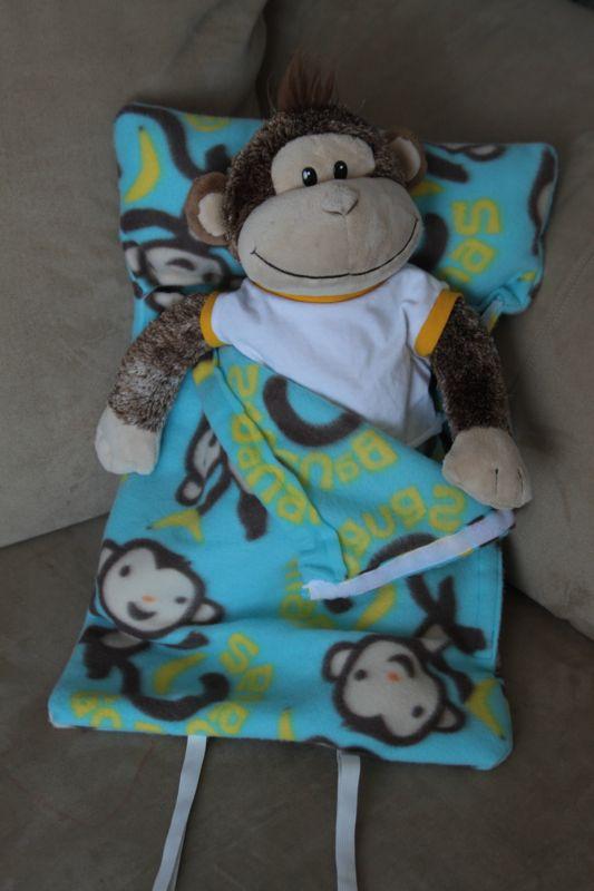 Stuffed monkey propped up inside a sleeping bag