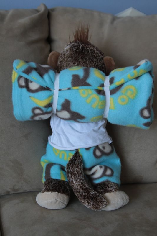 Stuffed animal monkey with sleeping bag rolled up on his back like a backpack