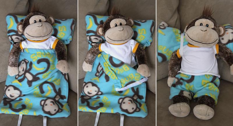 A stuffed animal monkey inside a sleeping bag