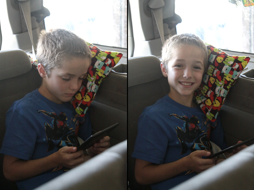 A young boy in a car leaning his head against small pillow