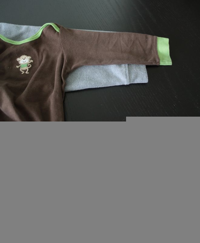 A baby shirt with sleeve placed over the mens sweater sleeve