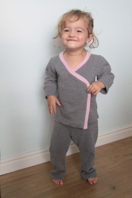 A little girl wearing gray and pink pajamas