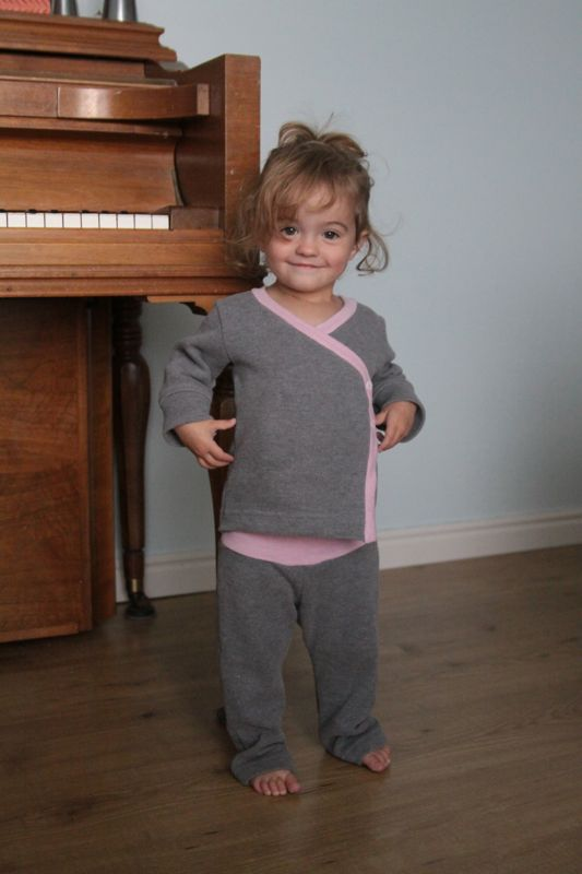 A little girl wearing a pair of wrap top pajamas made from a mens sweater