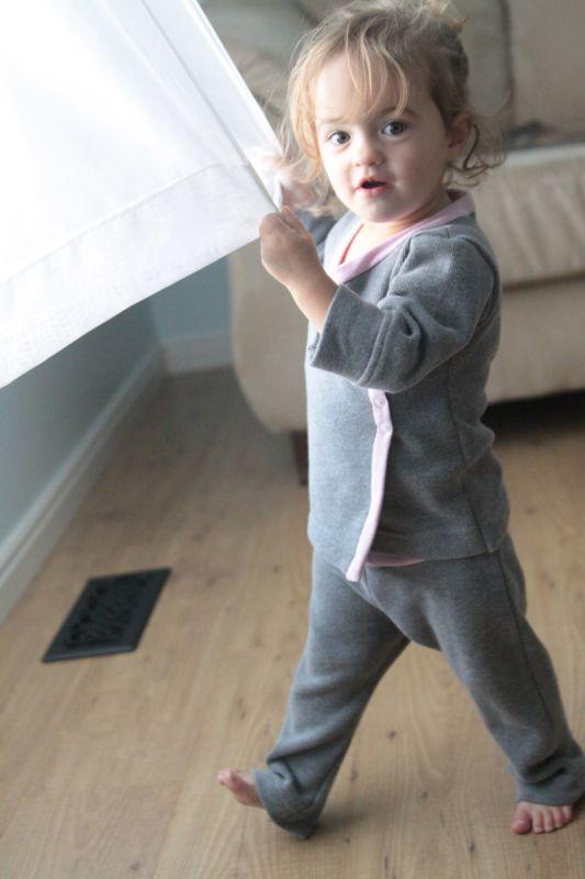 A little girl playing around wearing pajamas