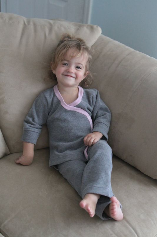 a little girl wearing gray pajamas with pink trim