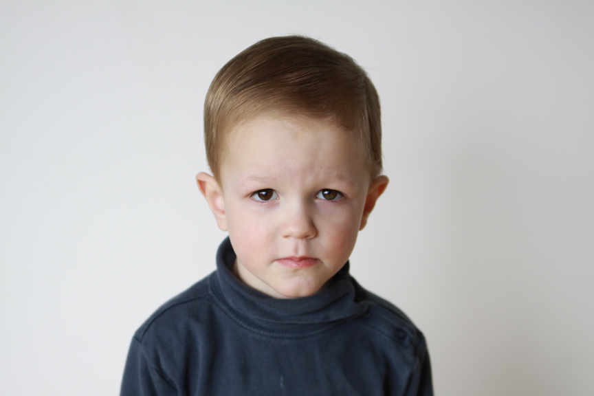 A young boy with a sad expression looking at the camera