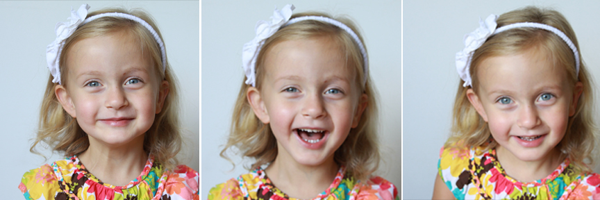 A toddler girl laughing and looking at the camera