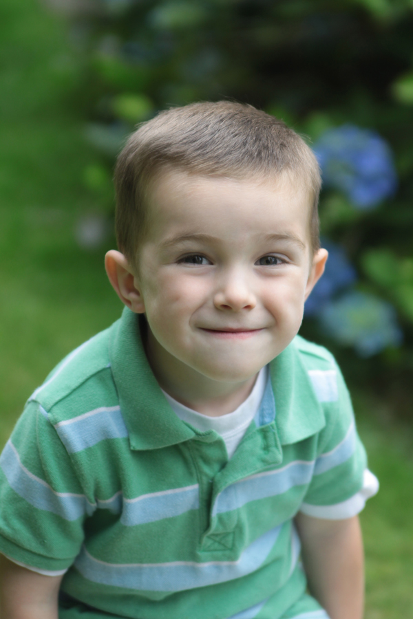 A toddler boy making a fake smile for the photograph