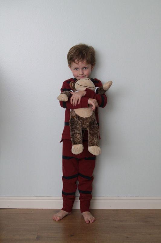 Little boy in pajamas hugging stuffed monkey