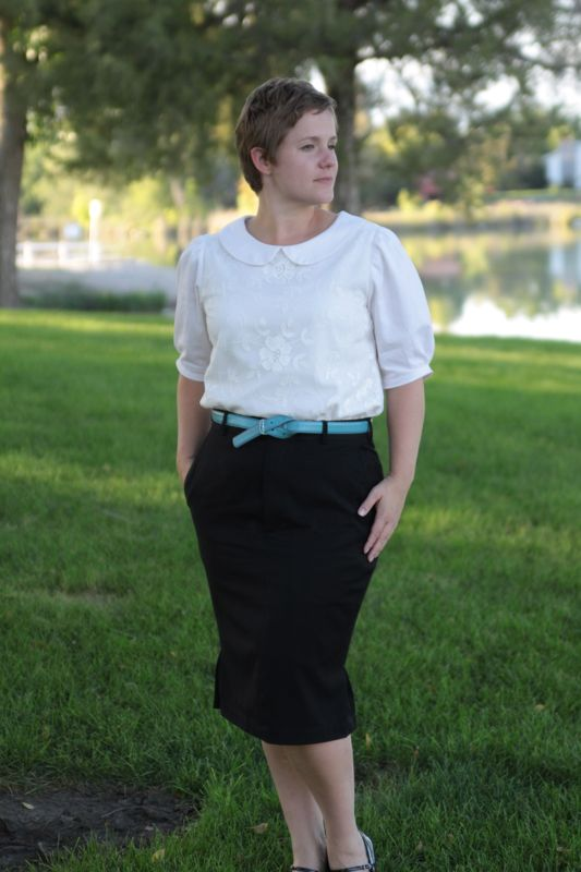 A woman in a white blouse and knee length black pencil skirt