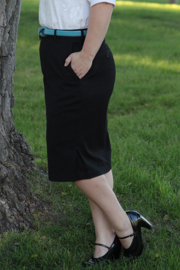 A woman wearing a black pencil skirt standing in the grass