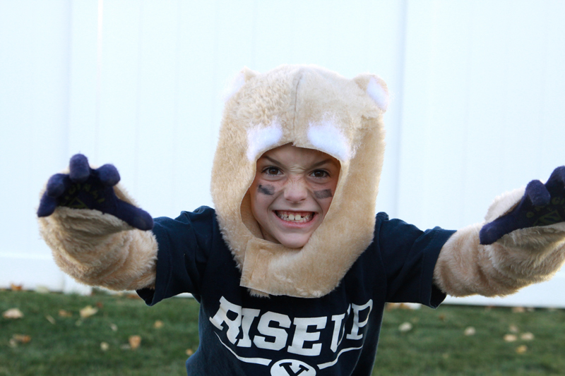 A little boy growling in a cosmo cougar costume