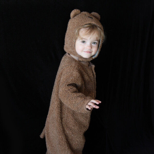 A little girl in a teddy bear costume with a plain black background