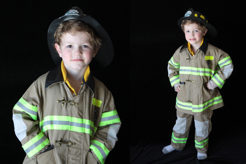 A young boy in a firefighter costume standing in front of a black background