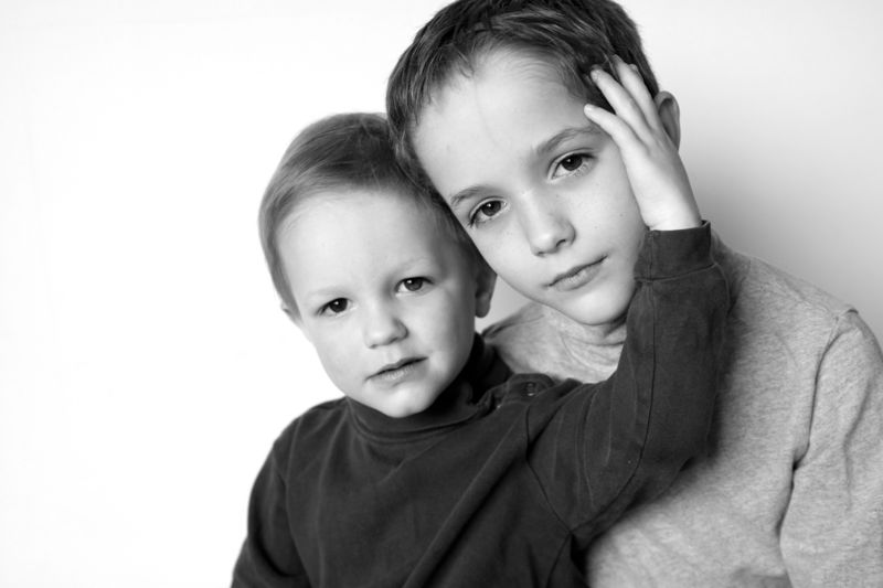 black and white photo of two little boys in front of a white background