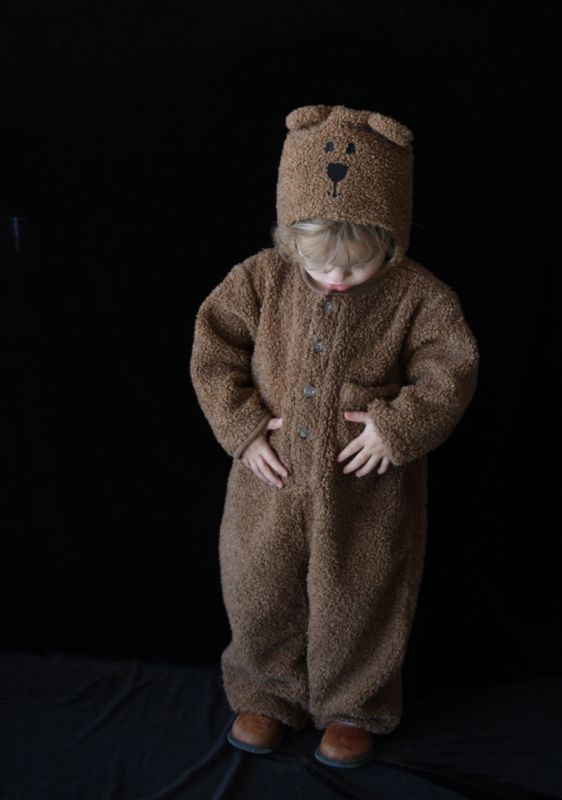 A little girl dressed up like a teddy bear in front of a black background