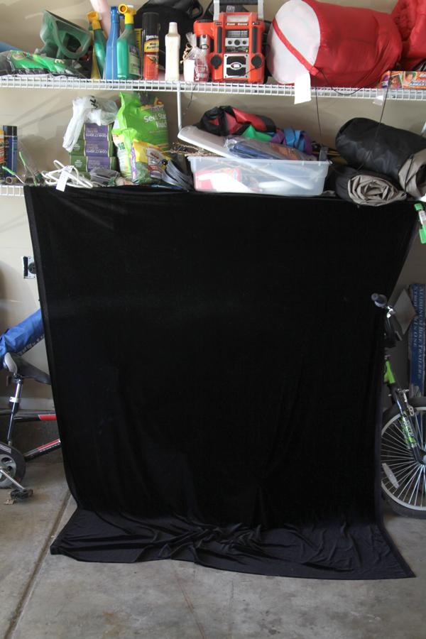 Black velvet fabric clamped to garage shelves