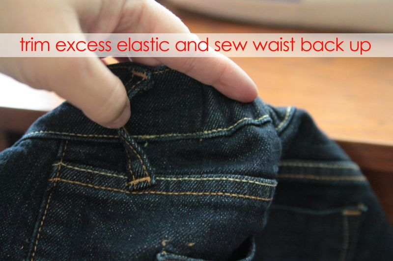 Hand holding gathered waistband of jeans