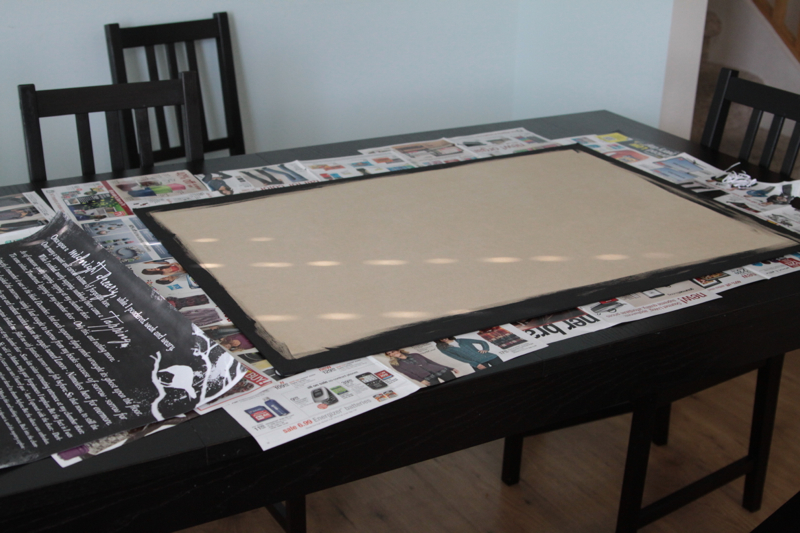 A large piece of MDF painted black around the edges on table covered in newspapers