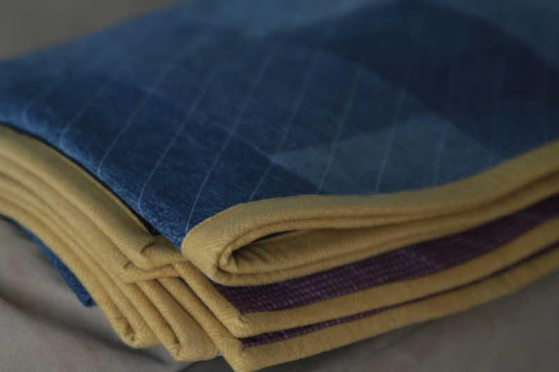 Close up of yellow edge binding on denim quilt