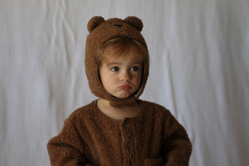 A baby girl in a teddy bear costume with wrinkled blanket background