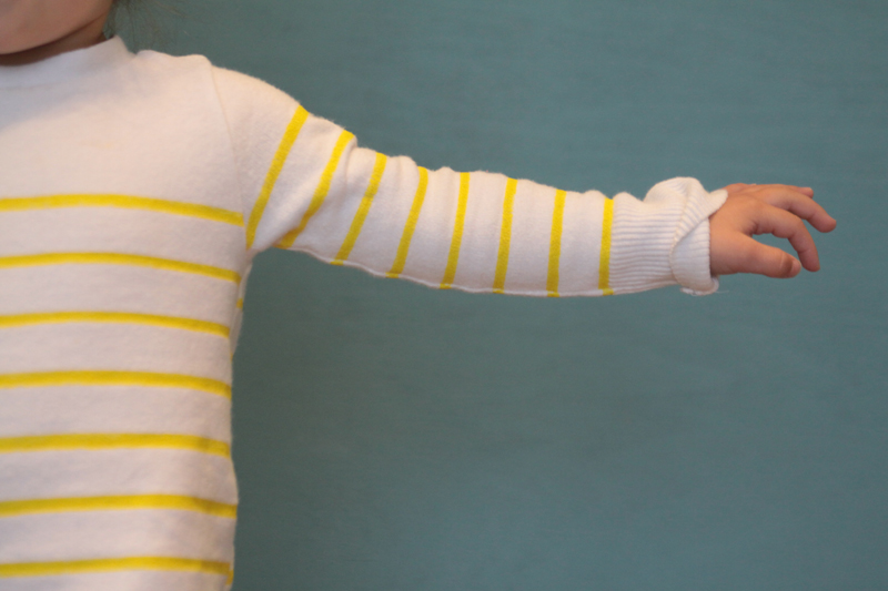 Close up of a white sweater sleeve with narrow yellow stripes