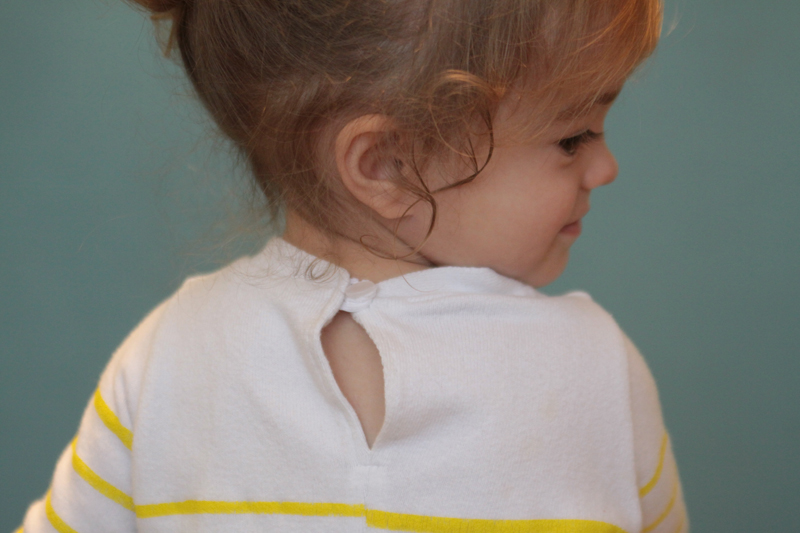 Back view of a girl\'s dress showing button closure