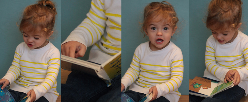A little girl wearing a white sweater with yellow stripes