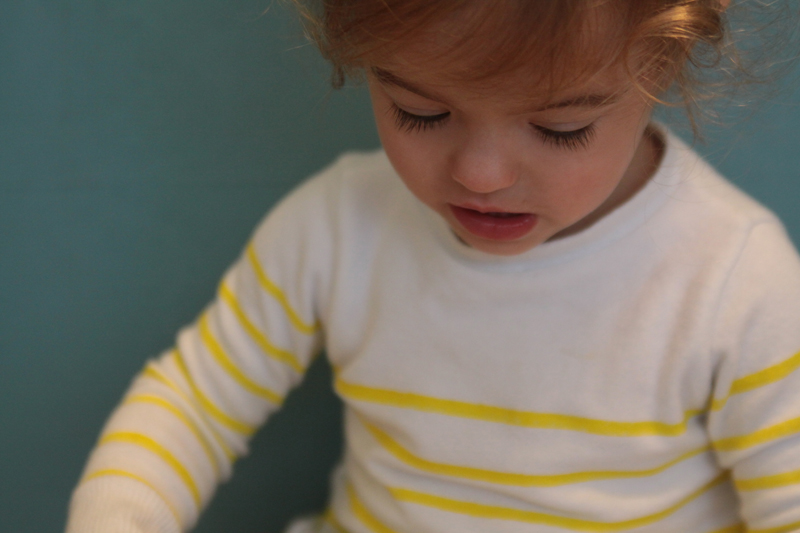 Closeup of little girl wearing white and yellow striped sweater