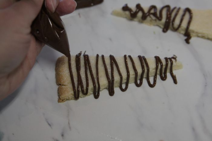 drizzling chocolate over pieces of shortbread