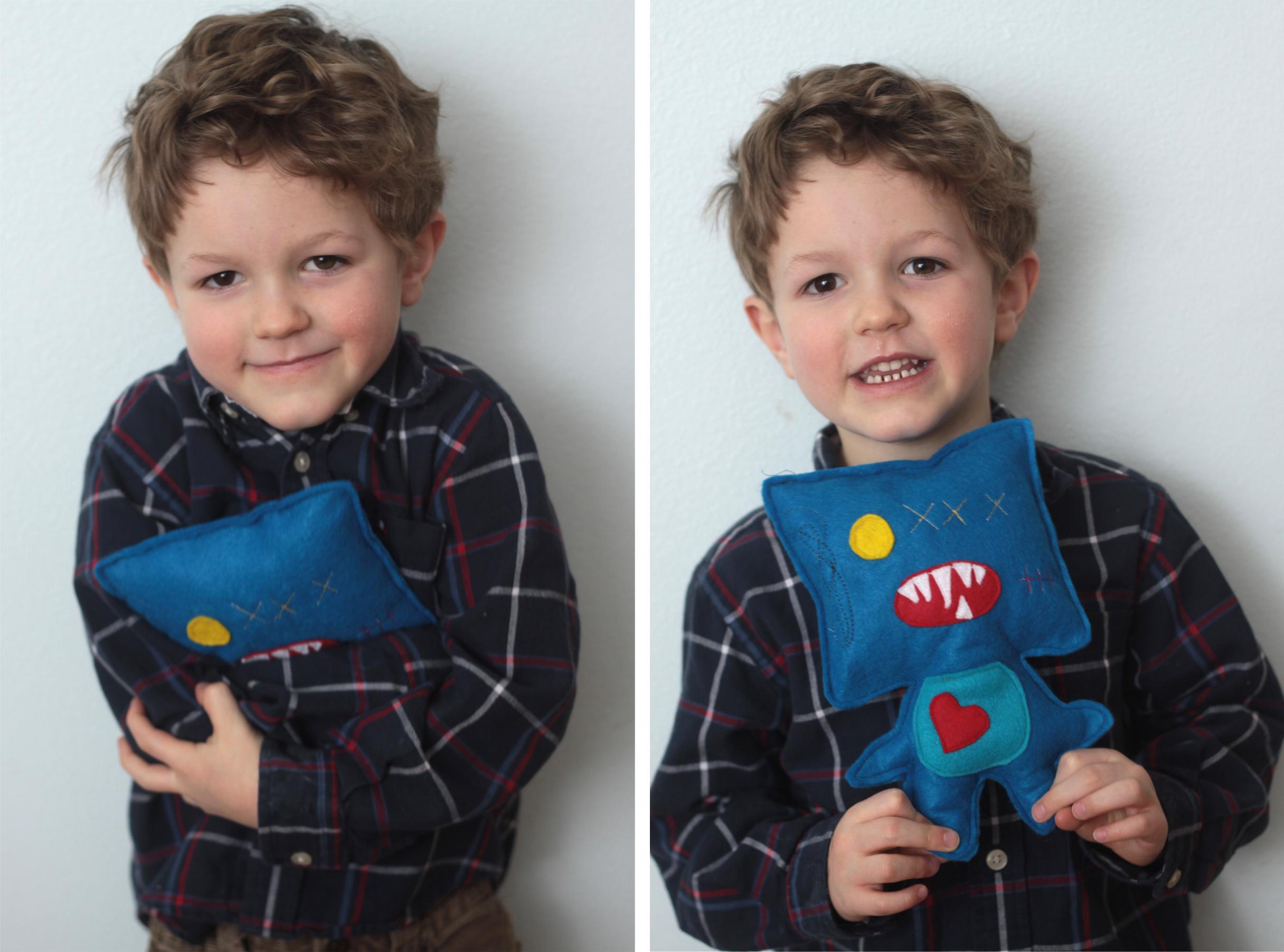 A little boy holding a felt monster he made