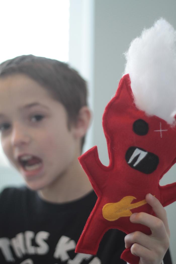 Boy holding a felt monster toy he made