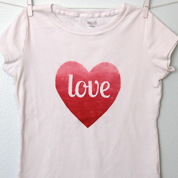 A t-shirt hanging on a line with a red heart and the word love on it