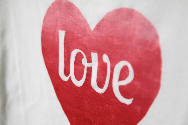 A close up of a red heart with word love on it