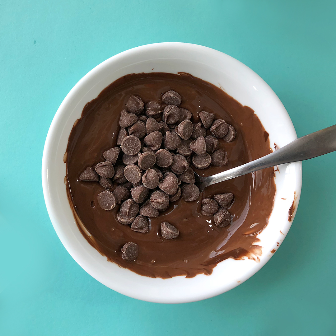 A bowl of melted chocolate chips with a handful of unmelted chocolate chips on top