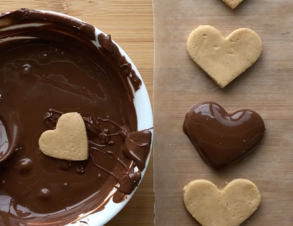 Peanut butter hearts on wax paper with melted chocolate, one heart dipped in chocolate