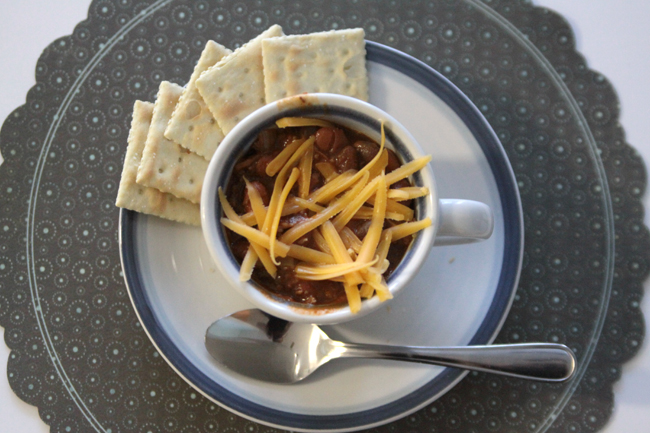 chili in a teacup with cheese and crackers