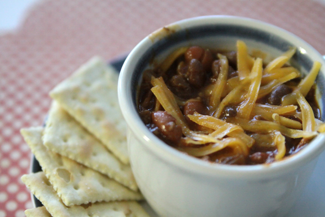A bowl of chili with cheese on top