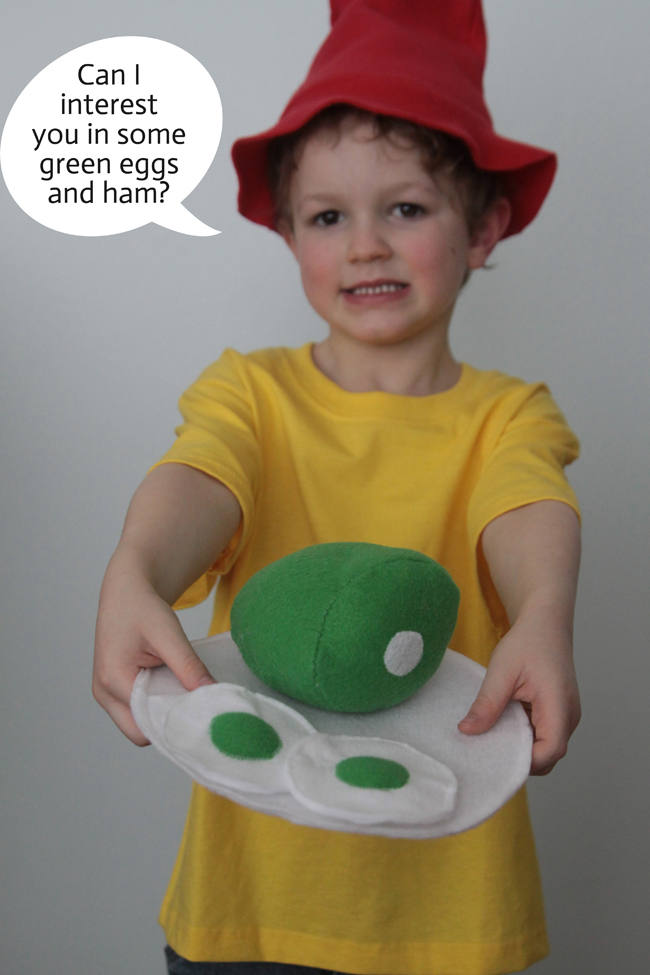 A little boy that is holding green eggs and ham