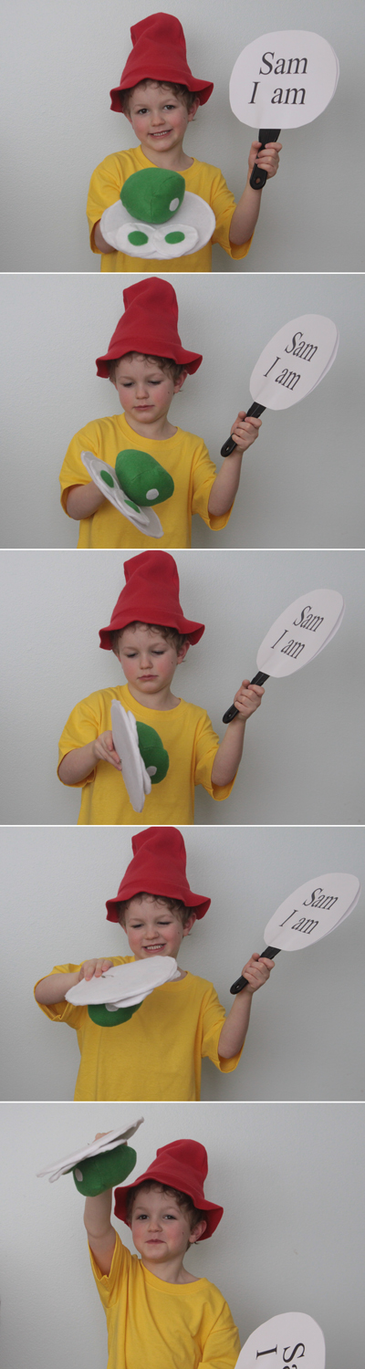 A young boy wearing a Green Eggs and Ham Dr. Suess costume