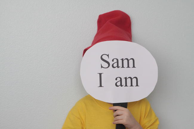 A boy holding a sign that says Sam I am